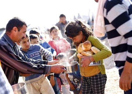 Kurdish refugee children from the Syrian town of Kobani receive food in a camp in the southeastern town of Suruc on the Turkish-Syrian border, October 18, 2014. REUTERS/Kai Pfaffenbach