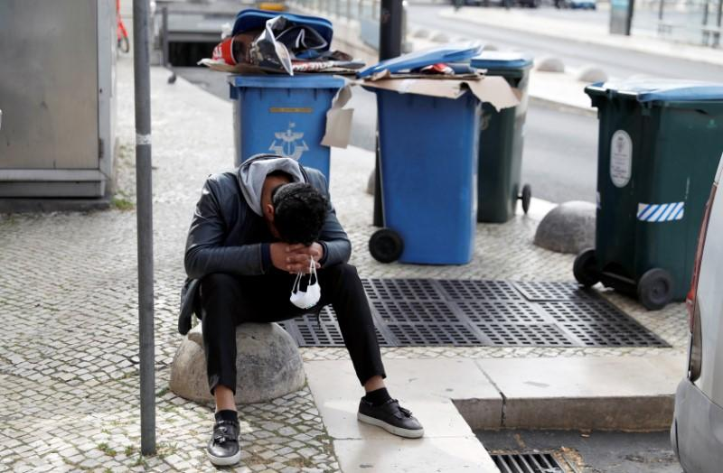 A man holds a protective mask in his hands as he rests at Restauradores Square in downtown Lisbon