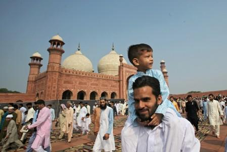 A boy sits on the shoulder of his father as they leave after attending the Eid al-Adha prayer at the Badshahi Mosque in Lahore
