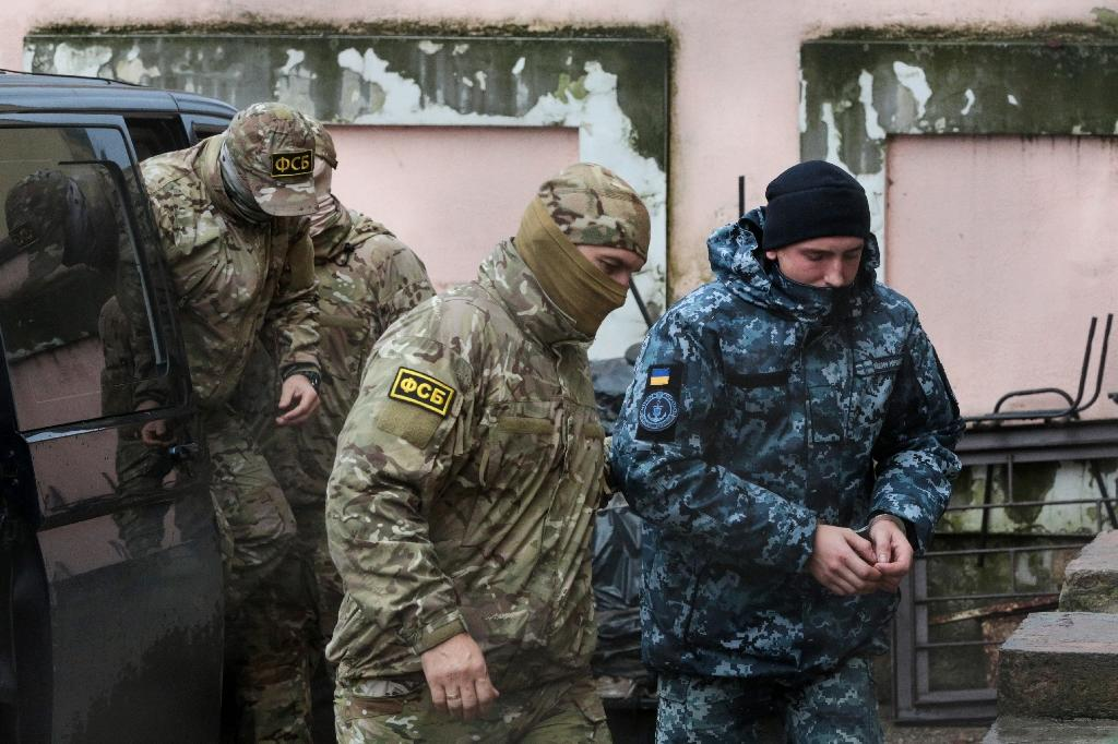 A Russian FSB security service officer escorts a detained Ukrainian sailor in Crimea in November -- a total of 24 sailors are still being held by Russia along with three naval vessels from Ukraine (AFP Photo/STR)