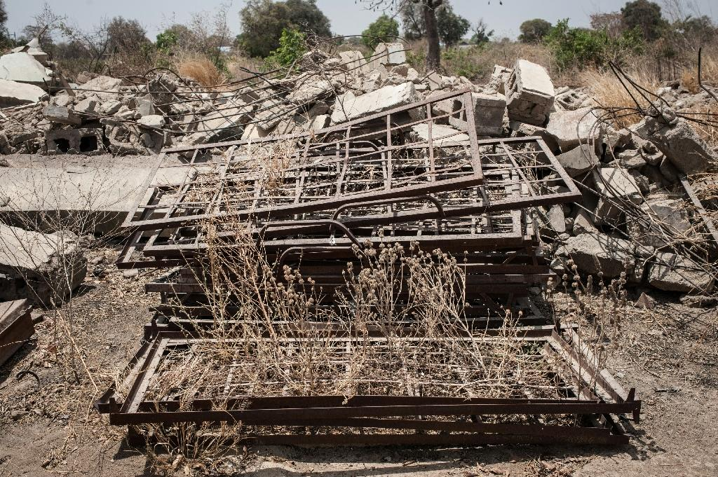 Bed fames are stacked in a pile outside the demolished dormitories of the former Government Girls Secondary School of Chibok in Nigeria on March 25, 2016 (AFP Photo/Stefan Heunis)