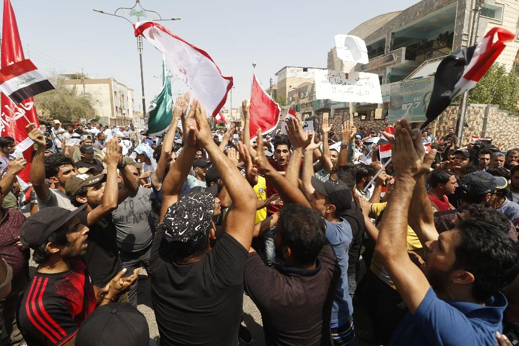 Iraqis chant slogans during a protest in the southern city of Basra on August 5, 2018