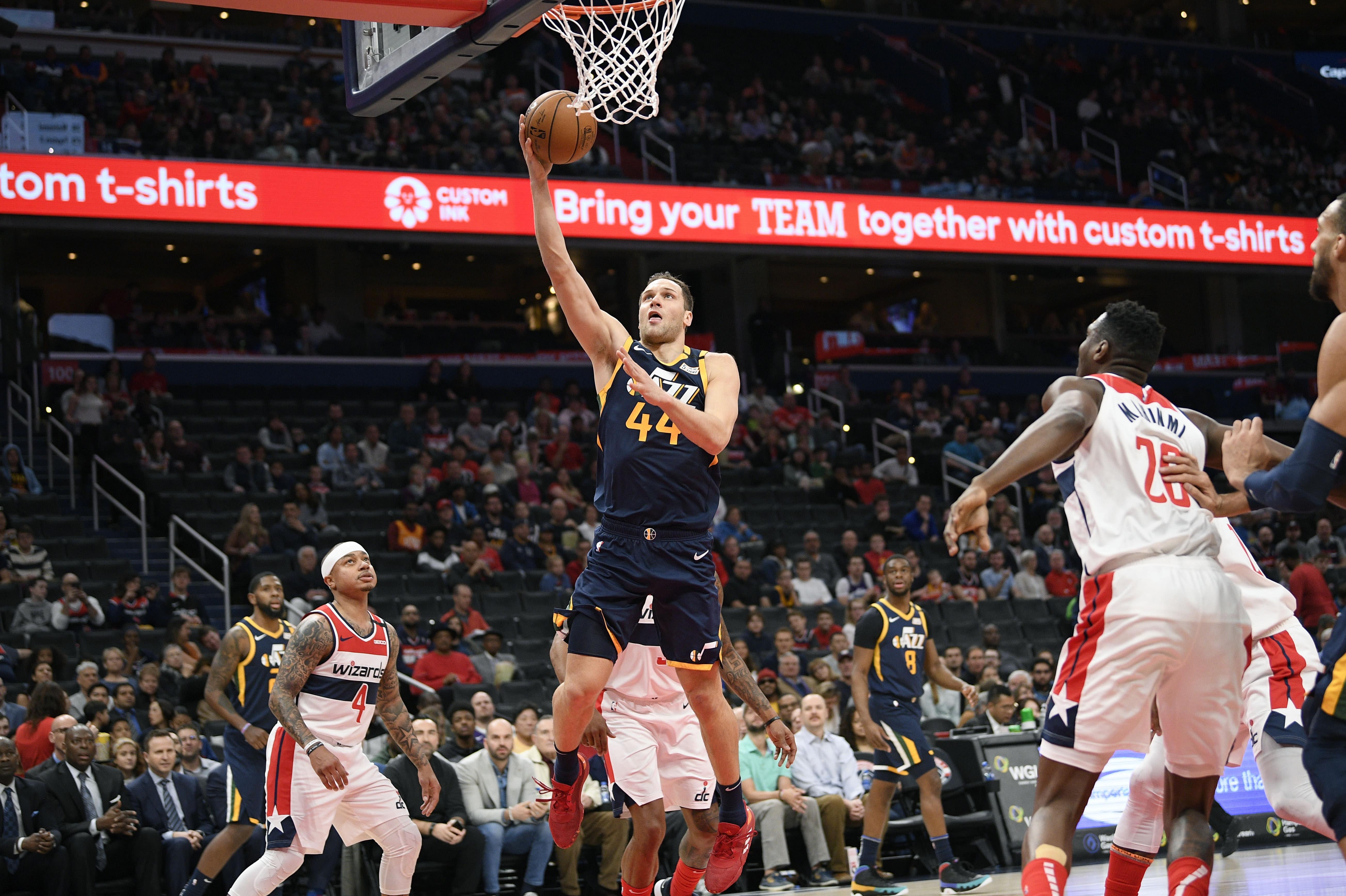 Utah Jazz forward Bojan Bogdanovic (44) goes to the basket against Washington Wizards guard Isaiah Thomas (4) and center Ian Mahinmi (28) during the first half of an NBA basketball game, Sunday, Jan. 12, 2020, in Washington. (AP Photo/Nick Wass)