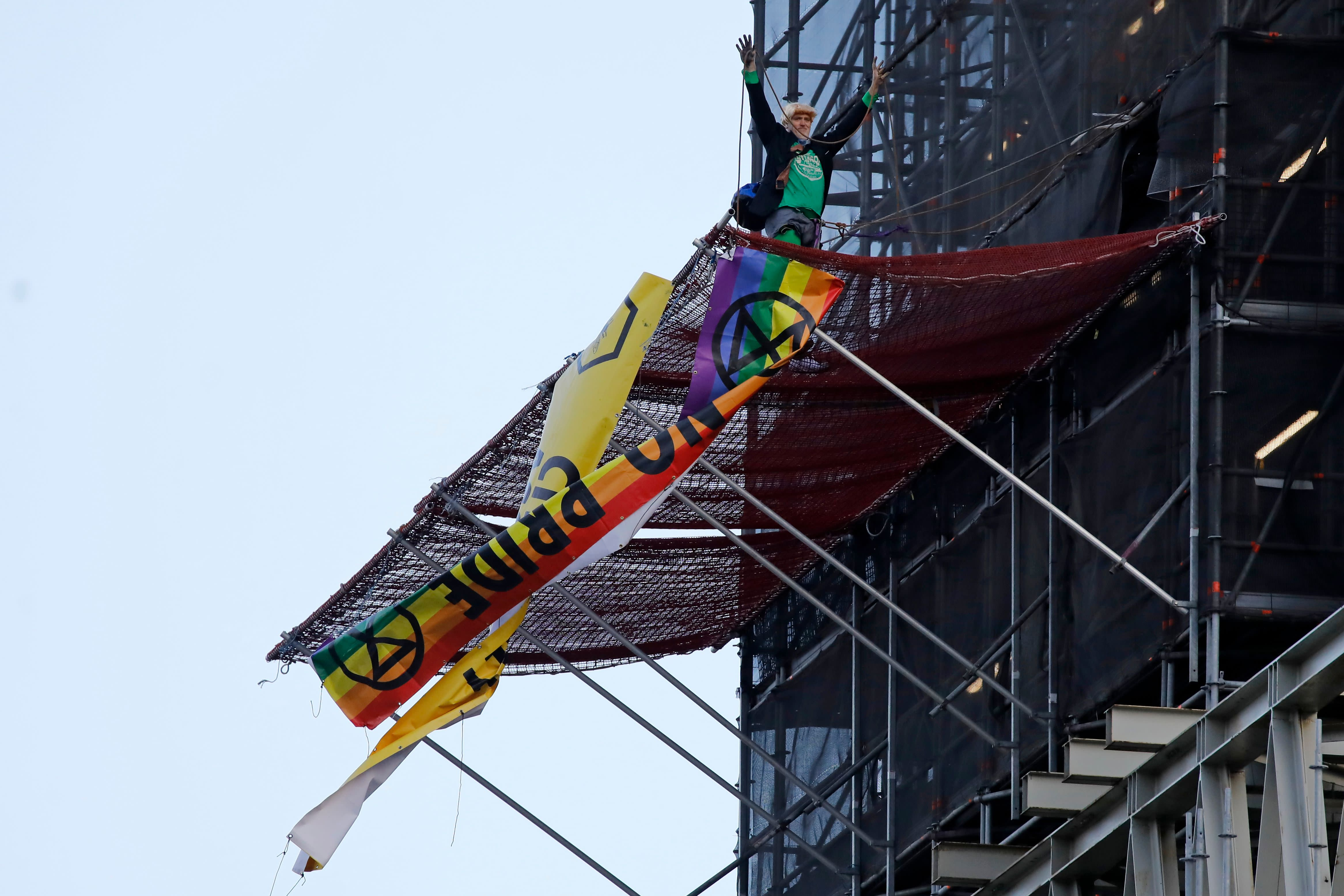 Extinction Rebellion activist dressed as Boris Johnson climbs up Big Ben in climate change protest