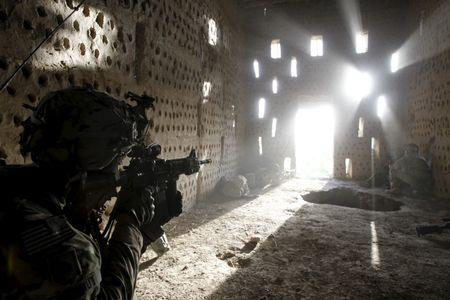 U.S. soldier Nicholas Dickhut from 5-20 infantry Regiment attached to 82nd Airborne points his rifle at a doorway after coming under fire by the Taliban while on patrol in Zharay district in Kandahar province, southern Afghanistan in this April 26, 2012 file photo. REUTERS/Baz Ratner/Files