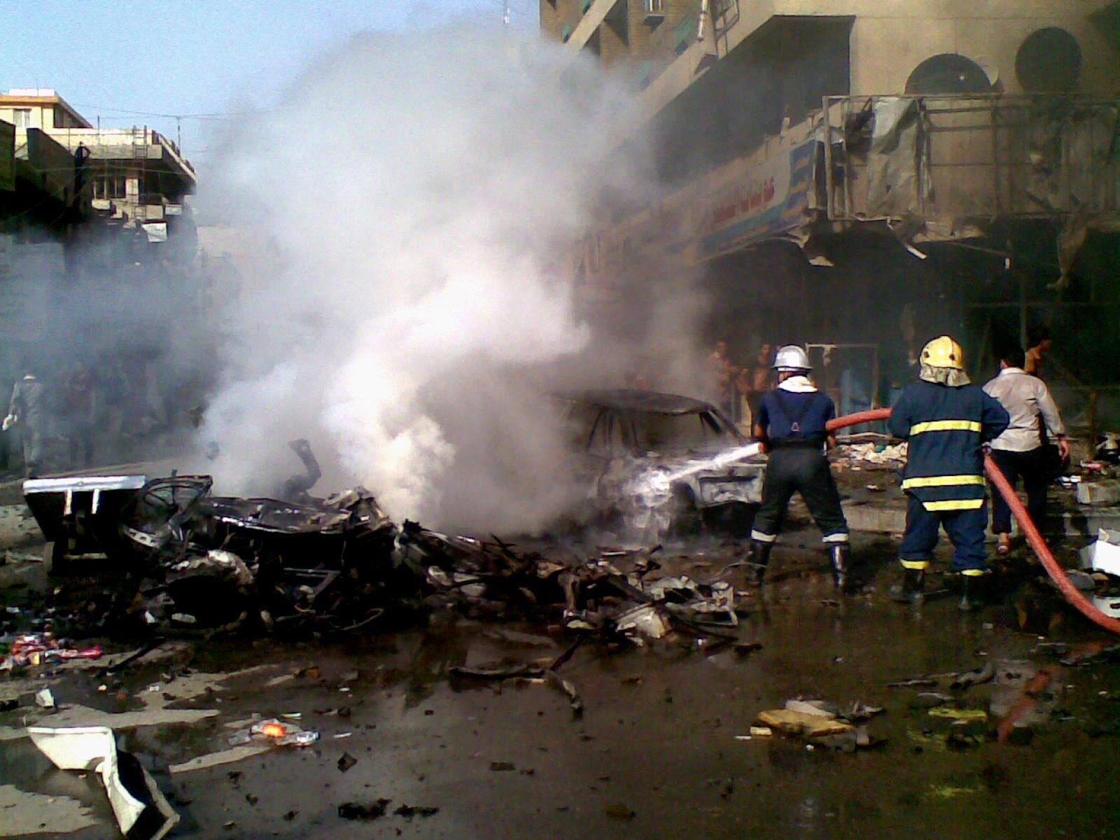 Iraqi firefighters distinguish a fire at the scene of a car bomb attack in Baghdad, Iraq, Monday, May 27, 2013. A parked car bomb explosion in the busy commercial Sadoun Street in central Baghdad, killed and wounded scores of people, police said. (AP Photo)