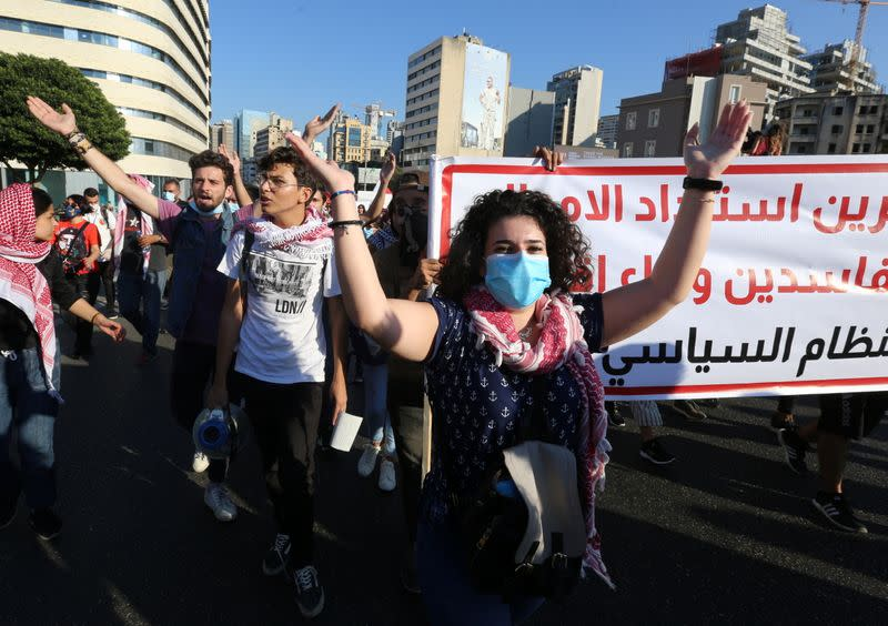 Anti-government demonstrators gesture during a protest as Lebanese mark one year since the start of nation-wide protests in Beirut