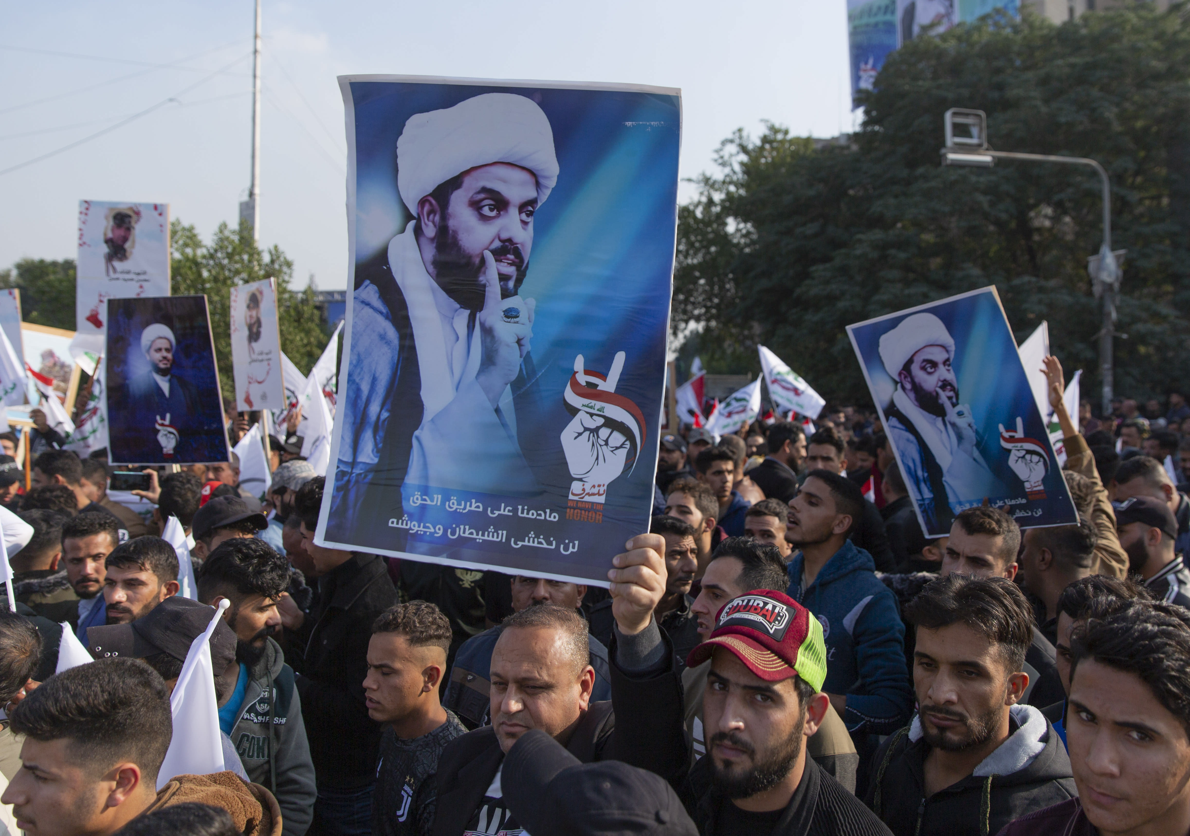 "Protesters chant anti US slogans and carry posters with pictures of Qais al-Khazali and Arabic that reads ""as long as we are on the track of the righteous, we will not be intimidated by the devil and it's armies,"" during a rally for the Shiite group Asaib Ahl al-Haq, in Baghdad, Iraq, Saturday, Dec. 14, 2019. (AP Photo/Nasser Nasser)"