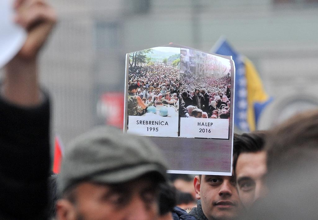 A young Bosnian man holds-up a comparison photo of Srebrenica 1995 and Aleppo 2016 as several thousands of Bosnian protestors gather to raise their voice against the killing in eastern Aleppo, Syria, during a rally in Sarajevo, on December 14, 2016 (AFP Photo/ELVIS BARUKCIC)