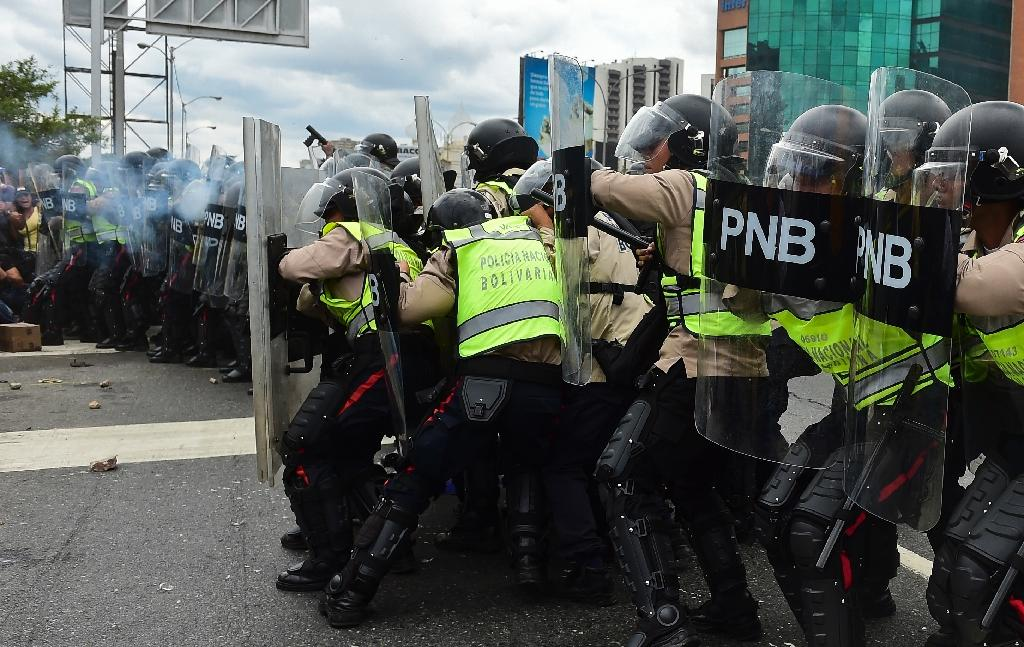 Demonstrators clash with police in an opposition march as they are blocked from reaching the National Electoral Court in Caracas to demand validation of the signatures to initiate a recall referendum against President Nicolas Maduro, on June 7, 2016 (AFP Photo/Ronaldo Schemidt)