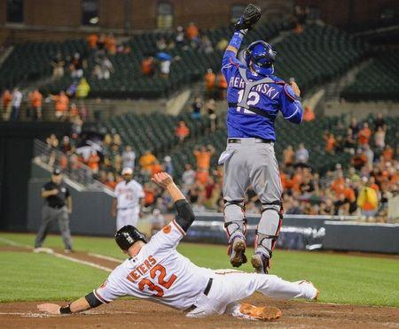 Orioles baserunner Wieters slides in safely as Rangers catcher Pierzynski reaches for the throw following McLouth's run-scoring base hit in the eighth inning off Rangers relief pitcher Frasor during their MLB American League baseball game in Baltimore