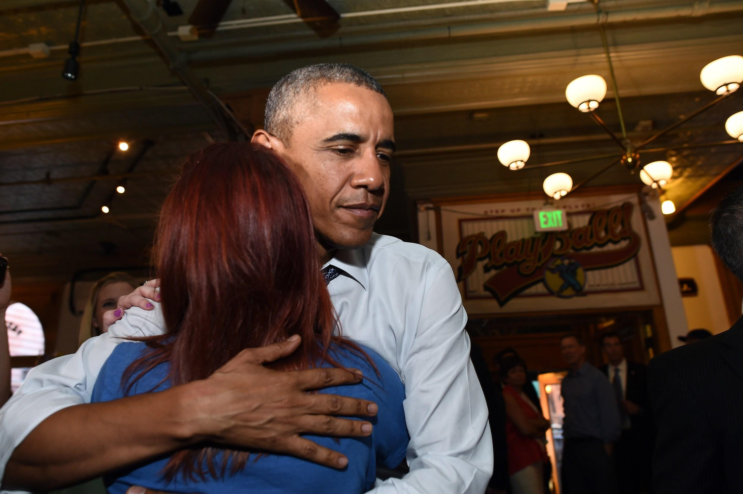 US President Barack Obama hugs Kalynne May Arrick from Tyler, Texas, after learning that her older brother Marine Sgt. Kenneth May had been killed in Afghanistan in 2010, at a pub in Denver, Colorado, on July 8, 2014. AFP PHOTO/Jewel Samad        (Photo credit should read JEWEL SAMAD/AFP/Getty Images)