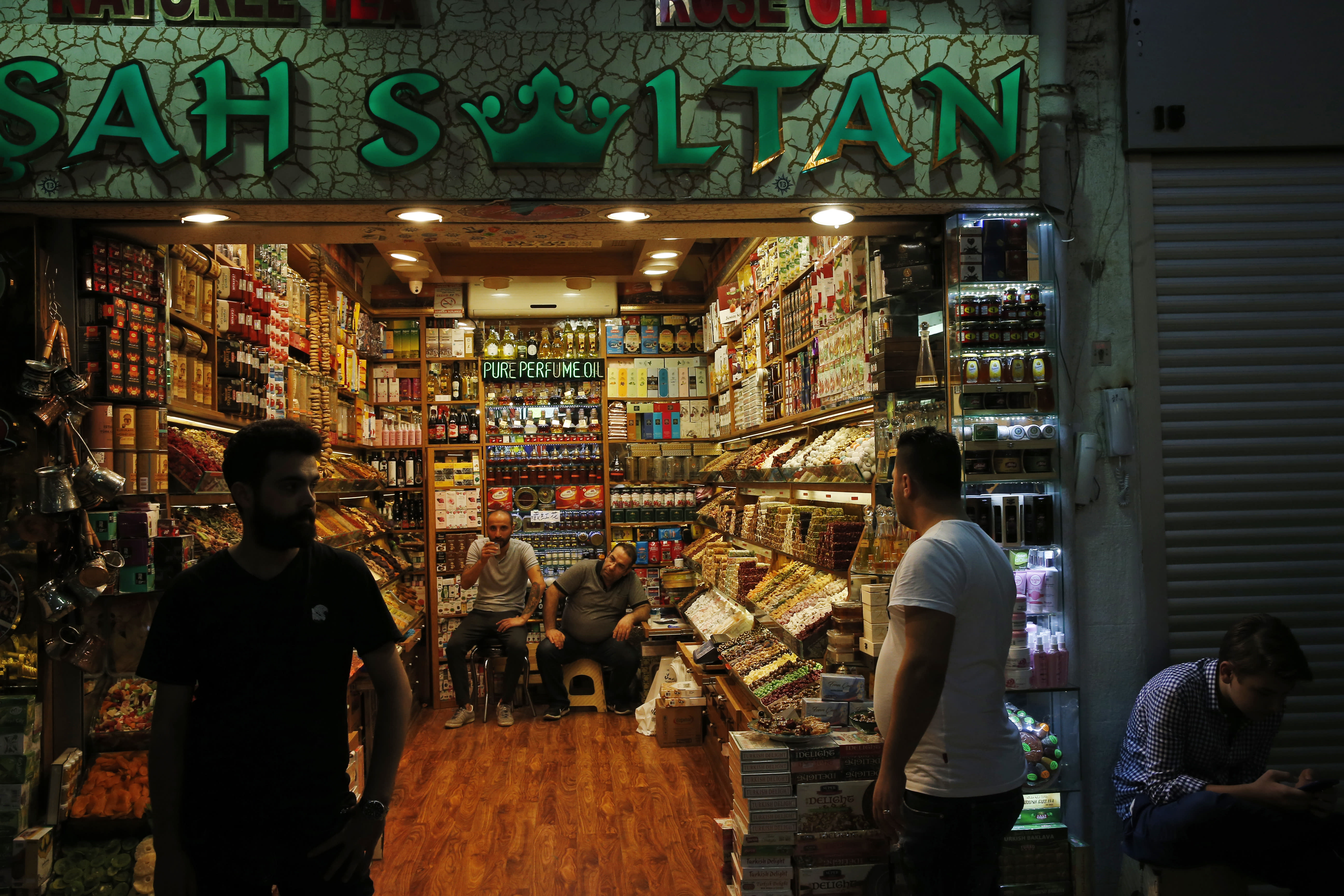 Shop owners wait for customers at Istanbul's Grand Bazaar, one of the city's main tourist attractions, Friday, Aug. 17, 2018. Turkey's lira currency fell once again, as Turkey and the United States exchanged new threats of sanctions Friday. (AP Photo/Lefteris Pitarakis)