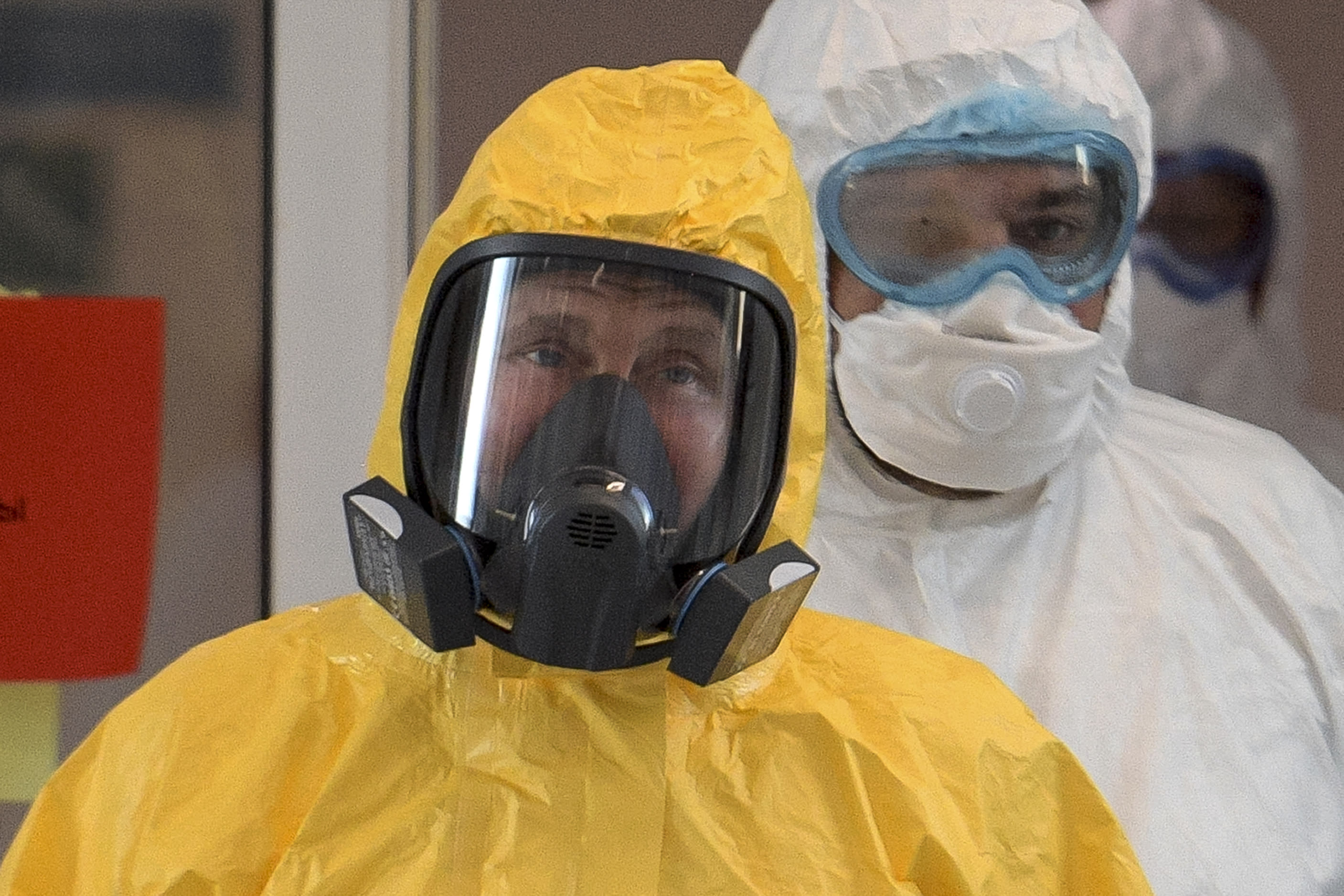 Russian President Vladimir Putin wearing a protective suit enters a hall during his visit to the hospital for coronavirus patients in Kommunarka, outside Moscow, Russia, Tuesday, March 24, 2020. For some people the COVID-19 coronavirus causes mild or moderate symptoms, but for some it can cause severe illness including pneumonia. (Alexei Druzhinin, Sputnik, Kremlin Pool Photo via AP)