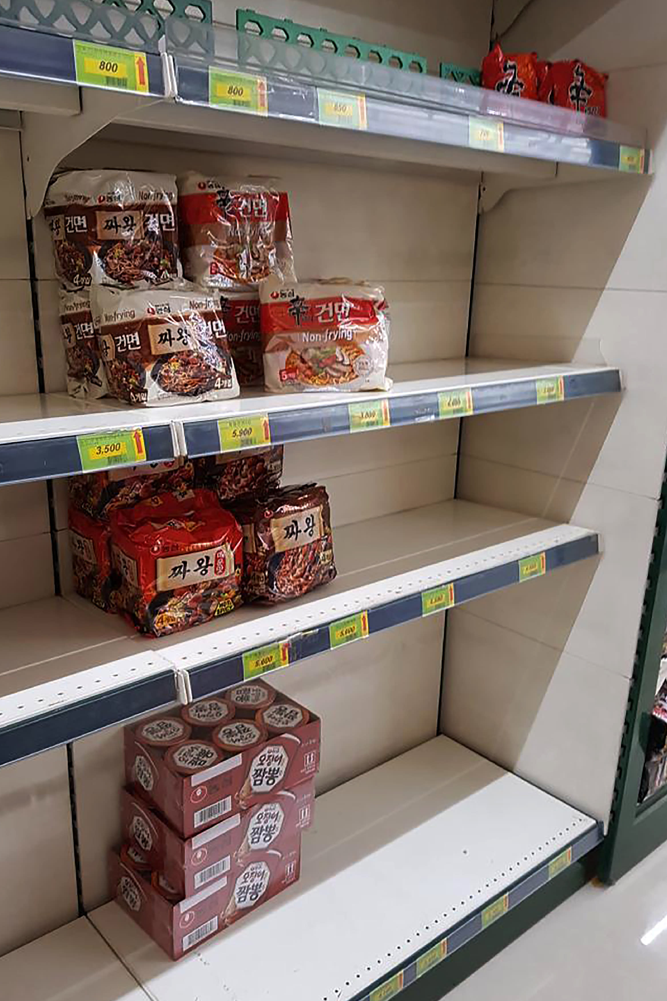 FILE - In this Feb. 21, 2020 file photo, Packages of instant noodles are displayed on almost empty shelves at a supermarket in Daegu, South Korea. As fears of a soaring viral outbreak grip the southeastern South Korean city of Daegu and nearby areas, many residents are struggling as they try to avoid the new virus. (AP Photo/Noh Yeo Jin, File)
