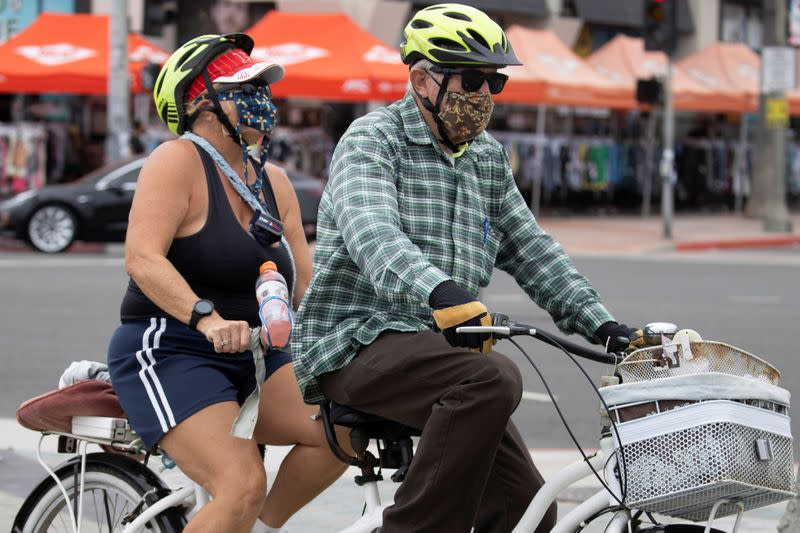 A couple chooses to wear face masks as they ride a tandem bike along the beach during the outbreak of the coronavirus disease (COVID-19), in Huntington Beach, California