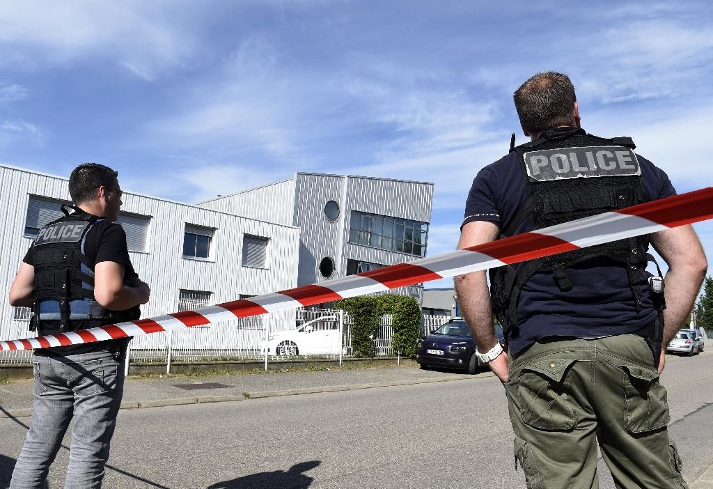 French police officers stand guard near a cordon outside the delivery service company in the industrial zone of Chassieu on June 26, 2015, where the victim who was decapitated worked