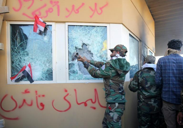 Members of Iraq's Hashed al-Shaabi, a mostly Shiite network of armed groups trained and armed by powerful neighbour Iran, smash a window at the US embassy in Baghdad in December 2019