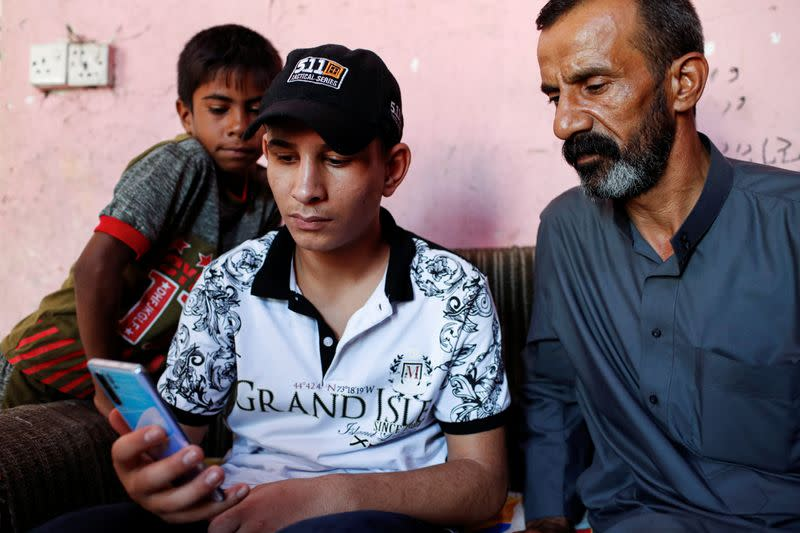 Iraqi teenager Hamid Saeed watches a video with his relatives that circulated on social media of him being mistreated by members of security forces, after being released from jail during an interview with Reuters at his home in Baghdad