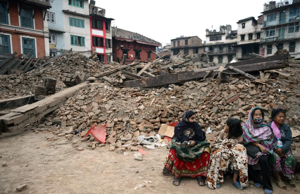 Nepalese residents sit near buildings severely damaged by an earthquake in Kathmandu, on April 26, 2015
