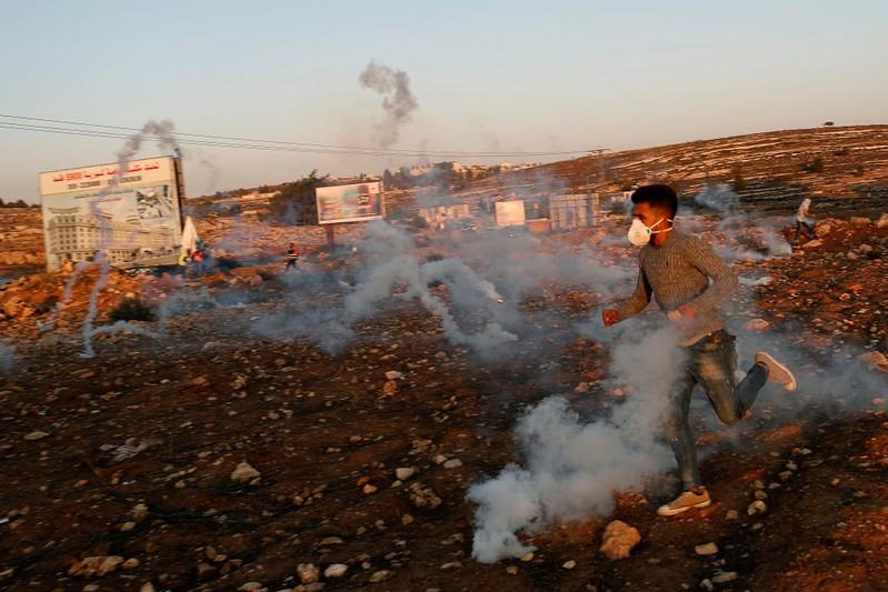 Palestinian demonstrator runs aways from tear gas fired by Israeli forces during an anti-Israel protest near the Jewish settlement of Beit El in the Israeli-occupied West Bank