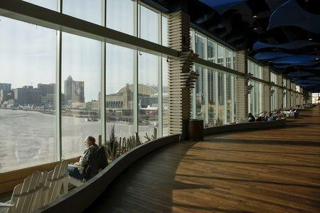 A man looks at the ocean through the windows of the Playground Pier, a luxury shopping mall, in Atlantic City, New Jersey January 20, 2016. REUTERS/Shannon Stapleton