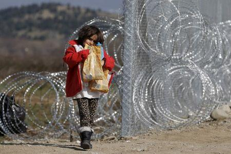 A migrant child from Afghanistan carries food next to a border fence at the Macedonian-Greek border in Gevgelija