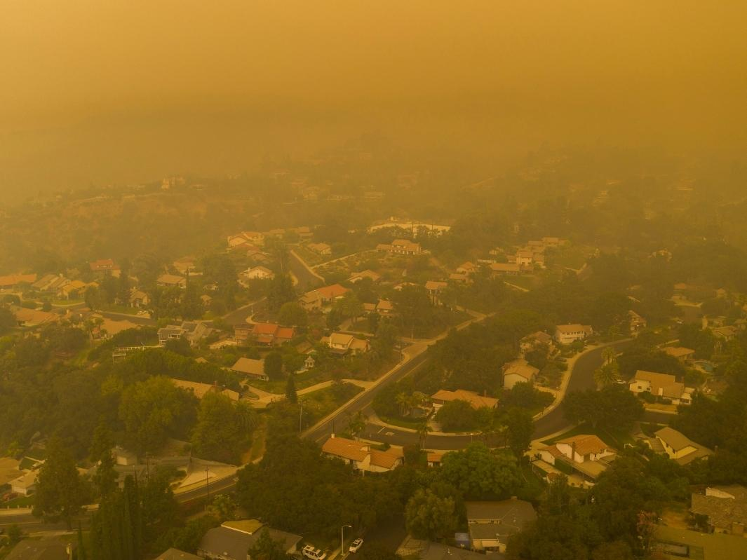 An aerial view shows neighborhoods enshrouded in smoke as the Bobcat Fire advances toward foothill cities and new evacuation order go into effect on September 13, 2020 in Monrovia, California.