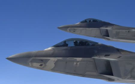 U.S. F-22 Raptor fighters fly alongside a KC-135 refueling plane over European airspace, during a flight from Britain to Mihail Kogalniceanu air base in Romania April 25, 2016. REUTERS/Toby Melville