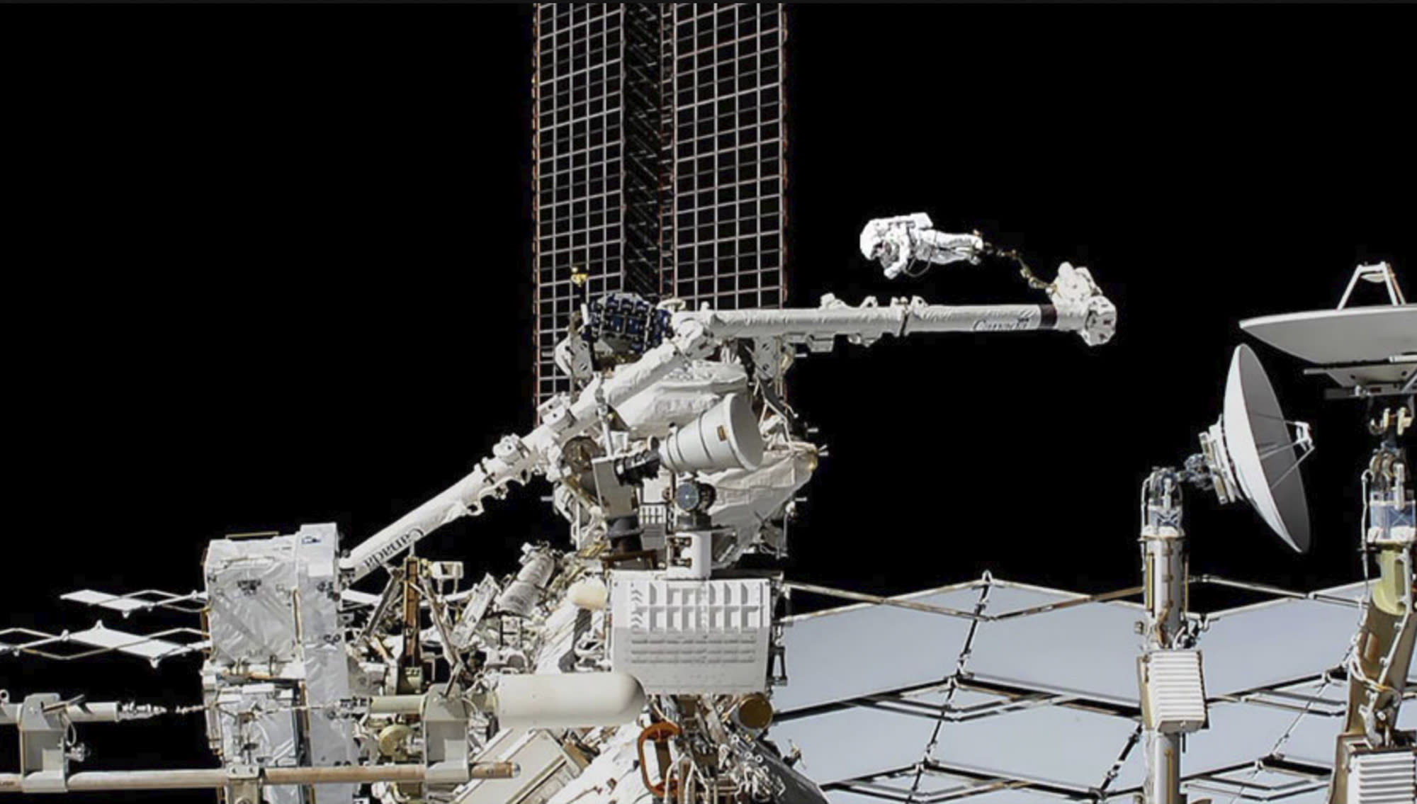 Spacewalking astronauts cutting into cosmic ray detector