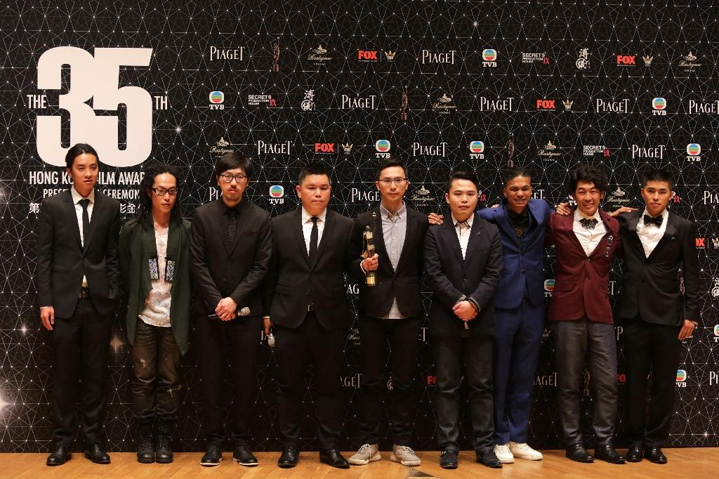 """The cast and crew of the controversial film """"Ten Years,"""" pose after winning best film at the Hong Kong Film Awards on April 3, 2016 (AFP Photo/Isaac Lawrence)"""