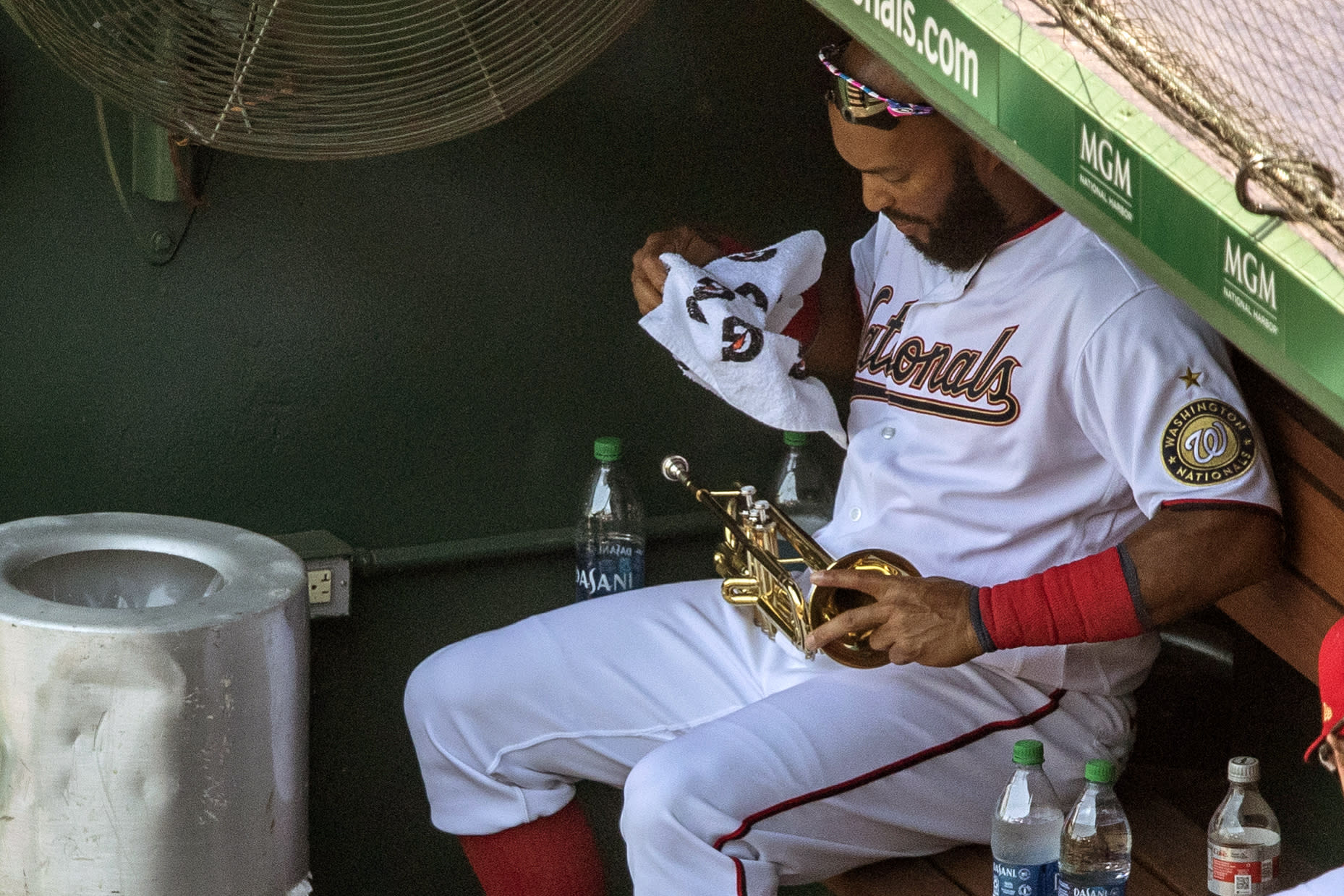 Washington Nationals' Emilio Bonifacio wipes his trumpet in the dugout during a baseball game against the New York Yankees at Nationals Park, Sunday, July 26, 2020, in Washington. (AP Photo/Alex Brandon)