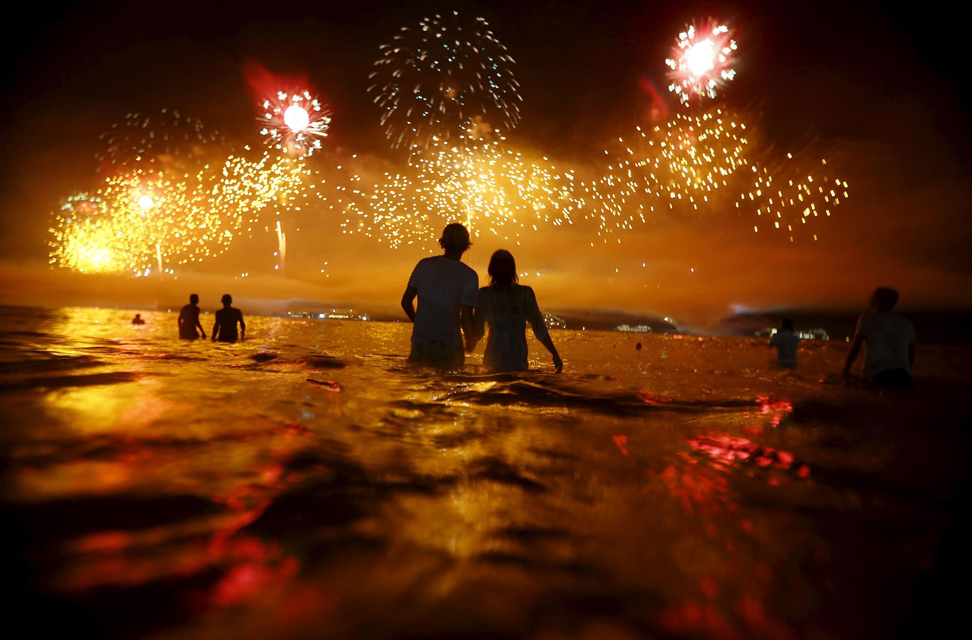 <p>JAN. 1, 2016 — People watch as fireworks explode over Copacabana beach during New Year celebrations in Rio de Janeiro, Brazil. (Ricardo Moraes/Reuters) </p>
