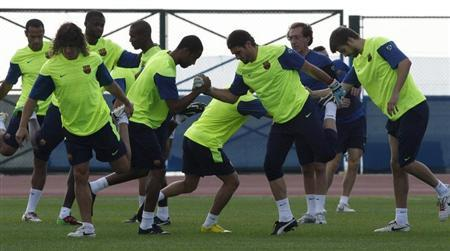 Members of the Barcelona team stretch during a training session in Abu Dhabi