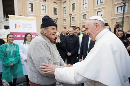 Pope Francis greets a man as he visits a first aid camp set up on the occasion of the World Day of the Poor in front of Saint Peter's square in Rome, Italy November 16, 2017. Osservatore Romano/Handout via Reuters