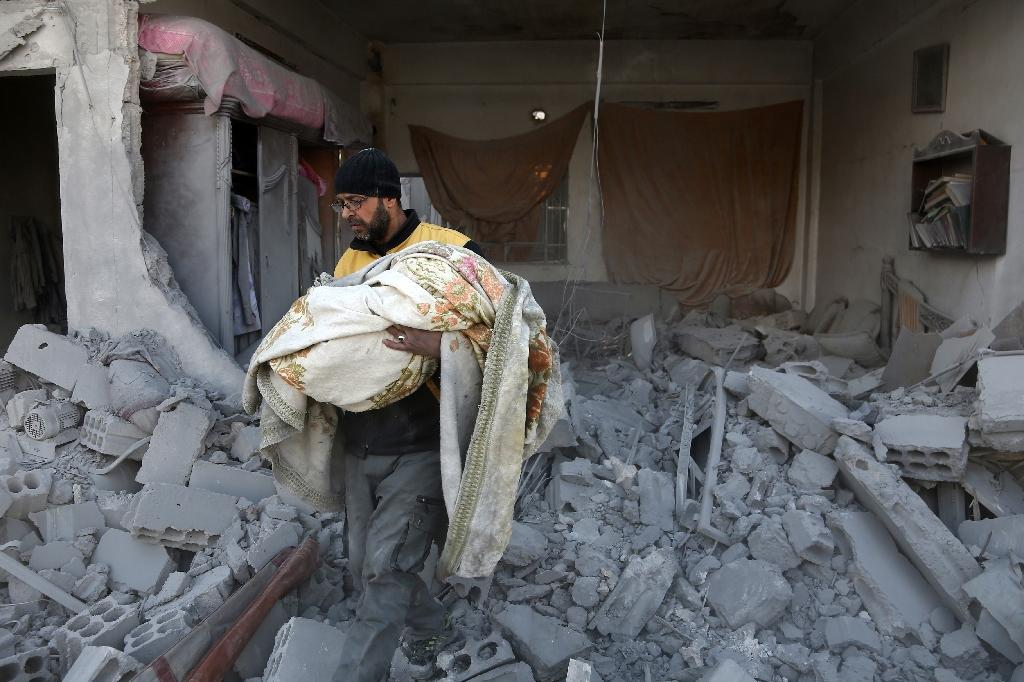 A member of the Syrian civil defence carries the body of a child out of the rubble of a house that was hit by a reported regime air strike in the rebel-held town of Jisreen, in the besieged Eastern Ghouta region on the outskirts of Damascus (AFP Photo/ABDULMONAM EASSA)
