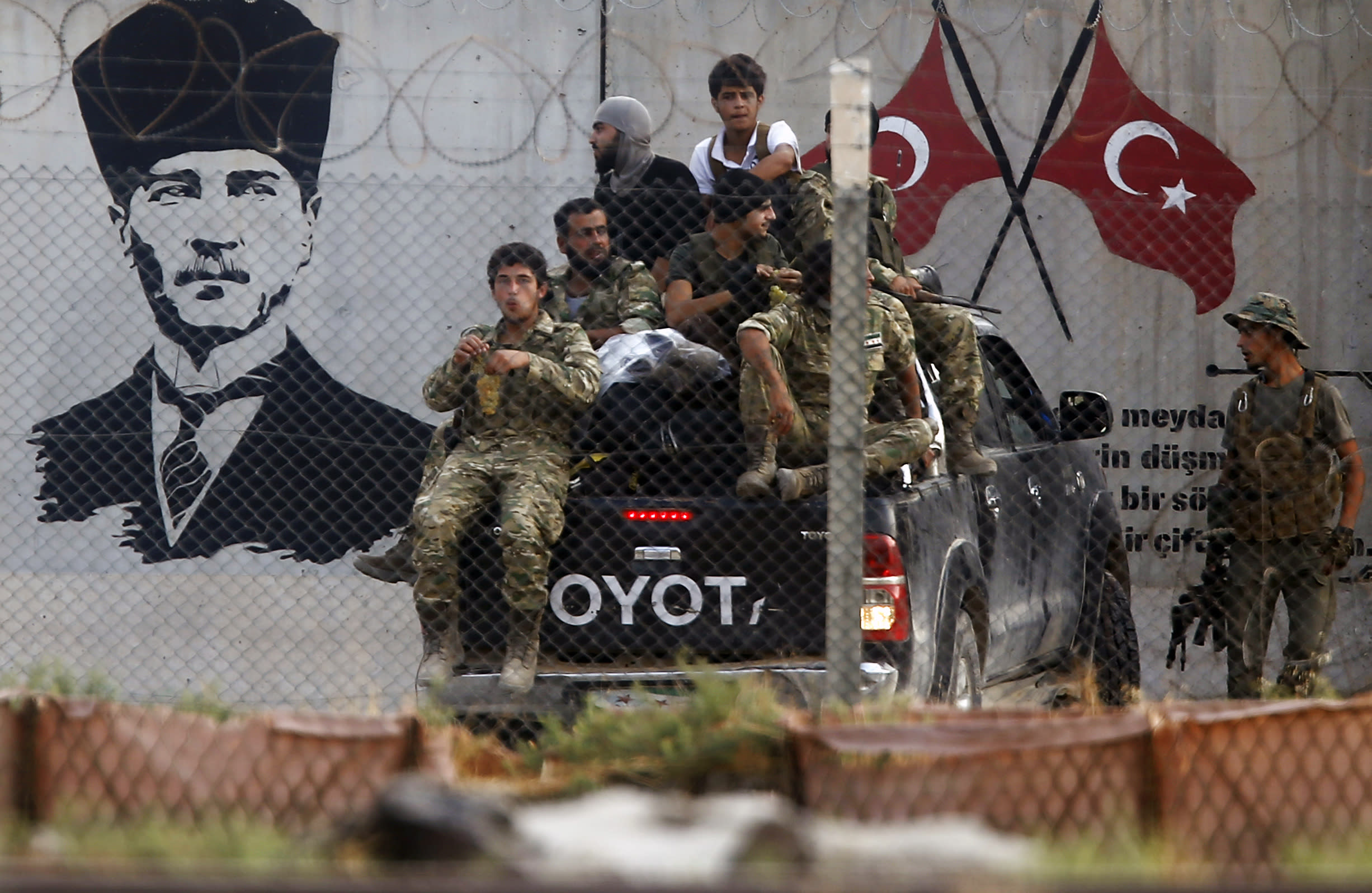 Turkish-backed Syrian opposition fighters on a pick up truck, drive past a graffiti of modern Turkey's founder Mustafa Kemal Ataturk as they cross the border between Turkey and Syria, in Akcakale, Sanliurfa province, southeastern Turkey, Thursday, Oct. 17, 2019. (AP Photo/Emrah Gurel)