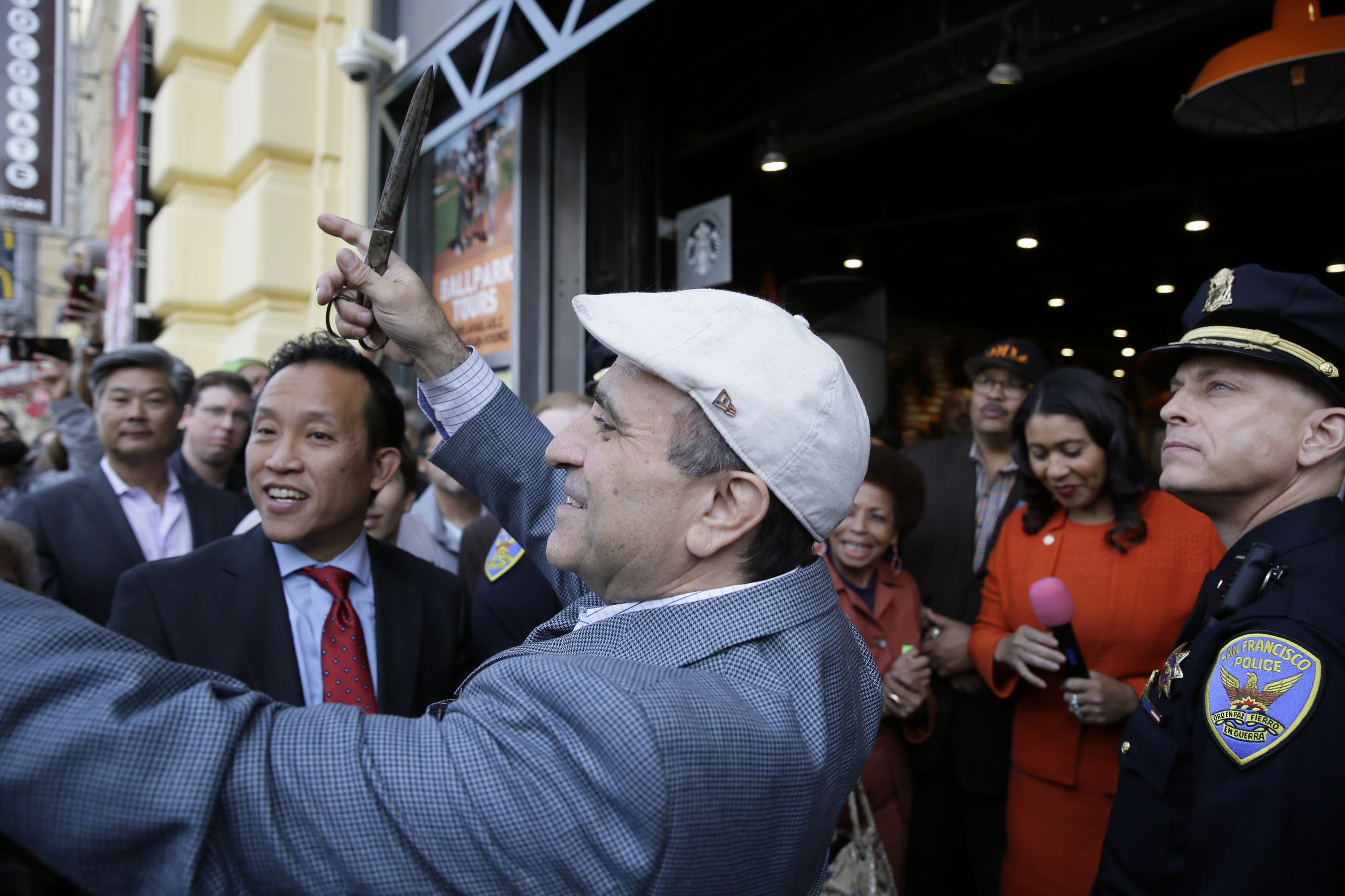 File - In this Nov. 20, 2018, file photo, owner Nick Bovis prepares to cut a ribbon during the opening of Lefty O'Doul's Baseball Ballpark Buffet & Café at Fisherman's Wharf in San Francisco. Looking on are state assemblyman David Chiu, second from left, San Francisco Mayor London Breed, second from right and city public works director Mohammed Nuru, third from right. A top San Francisco official in charge of cleaning up the city's notoriously filthy streets and a champion of adding more portable toilets has been arrested, jail records show. San Francisco Public Works Director Mohammed Nuru was taken into custody Monday, Jan. 27, 2020, along with Nick Bovis, the owner of Lefty O' Doul's, a longtime sports bar popular with tourists. Records say only that the men were arrested for felony safekeeping, which typically indicates federal charges. (AP Photo/Eric Risberg)