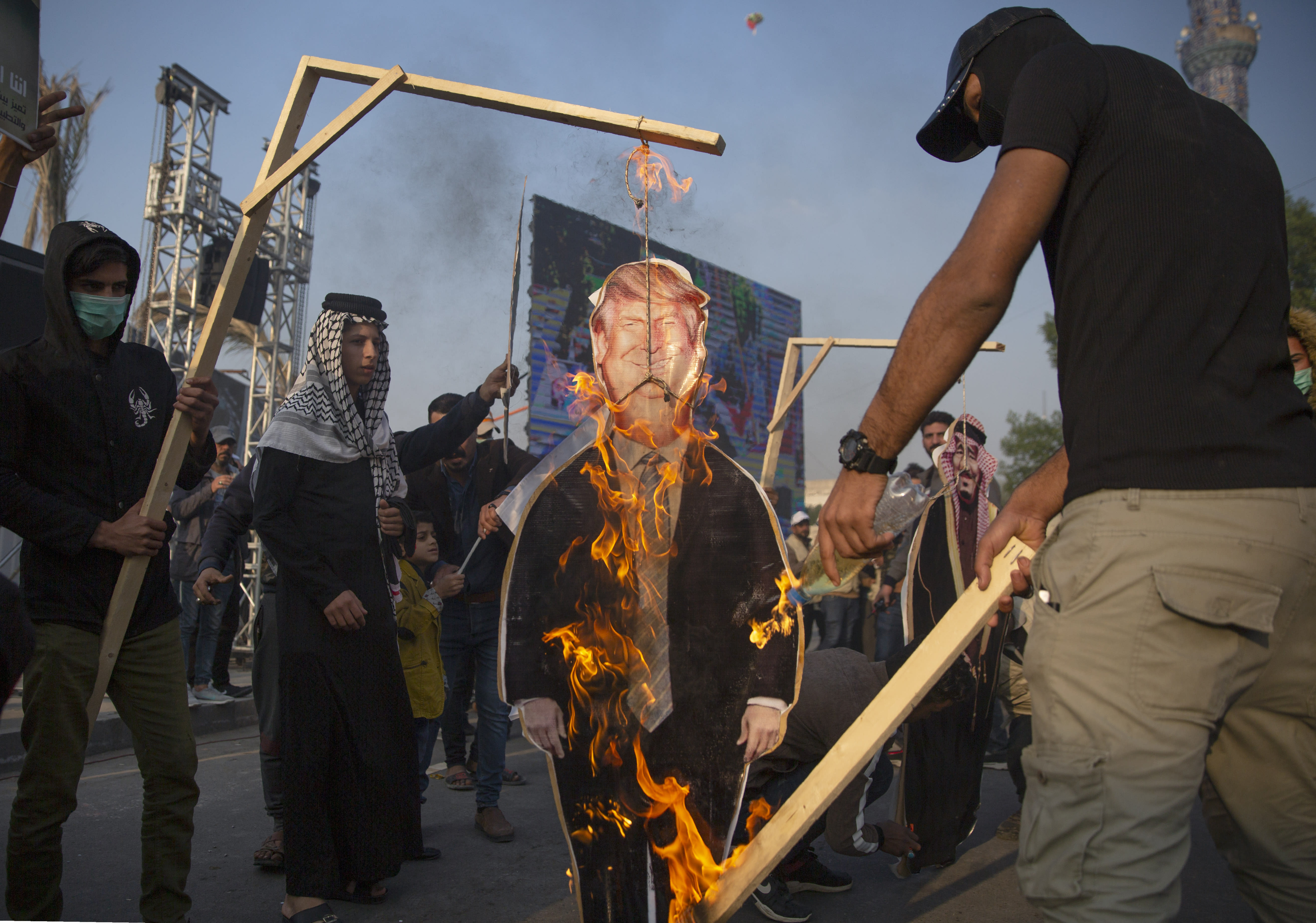 Protesters set on fire a cardboard cutout that depicts US President Donald Trump and hung to a gallows, during a rally for the Shiite group Asaib Ahl al-Haq, in Baghdad, Iraq, Saturday, Dec. 14, 2019. (AP Photo/Nasser Nasser)