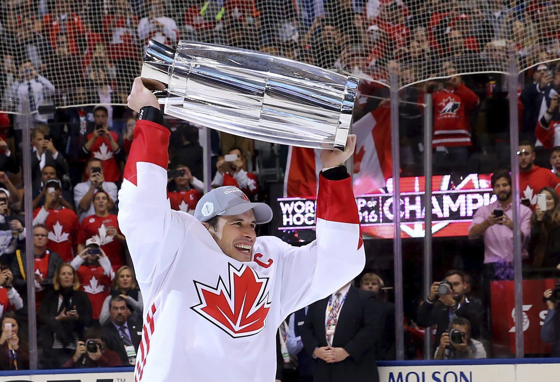 """FILE - In this Sept. 29, 2016 file photo, Canada's Sidney Crosby hoists the trophy following his team's victory over Europe in the World Cup of Hockey finals, in Toronto. The closest comparison to the NHL's summer restart is the 2016 World Cup of Hockey. Following a lengthy, unscheduled break because of a pandemic, teams have just two weeks of camp at home before traveling to Toronto or Edmonton for one exhibition game ahead of real competition.""""It's very similar to that,"""" Crosby said. """"You kind of have a short, abbreviated training camp and then you're right into it. You've got to be ready, but you also have to understand that you've just got to get better with every game."""" (Bruce Bennett/Pool Photo via AP, File)"""