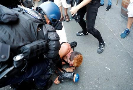 A demonstrator is detained after a protest march during the G7 summit, in Hendaye