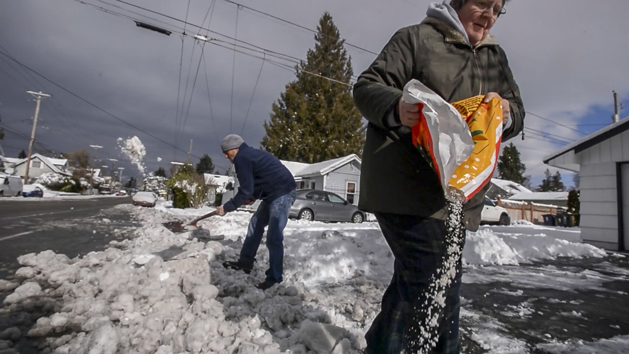 Sue Horgan, of Tacoma, salts her driveway as neighbor Michael Dane helps with the shoveling, Sunday, Feb. 10, 2019, in Tacoma, Wash. Pacific Northwest residents who are more accustomed to rain than snow were digging out from a winter storm and bracing for more on Sunday. (Peter Haley/The News Tribune via AP)
