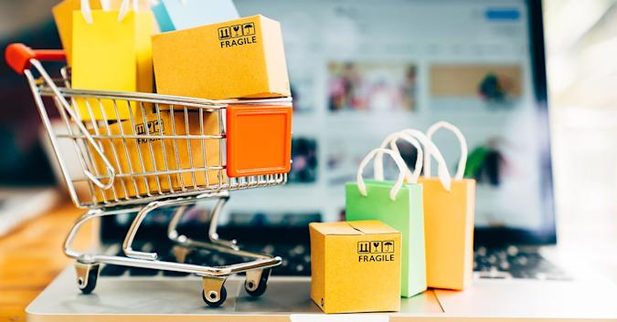 Stock image of a shopping cart full of boxes and packages, some marked fragile.