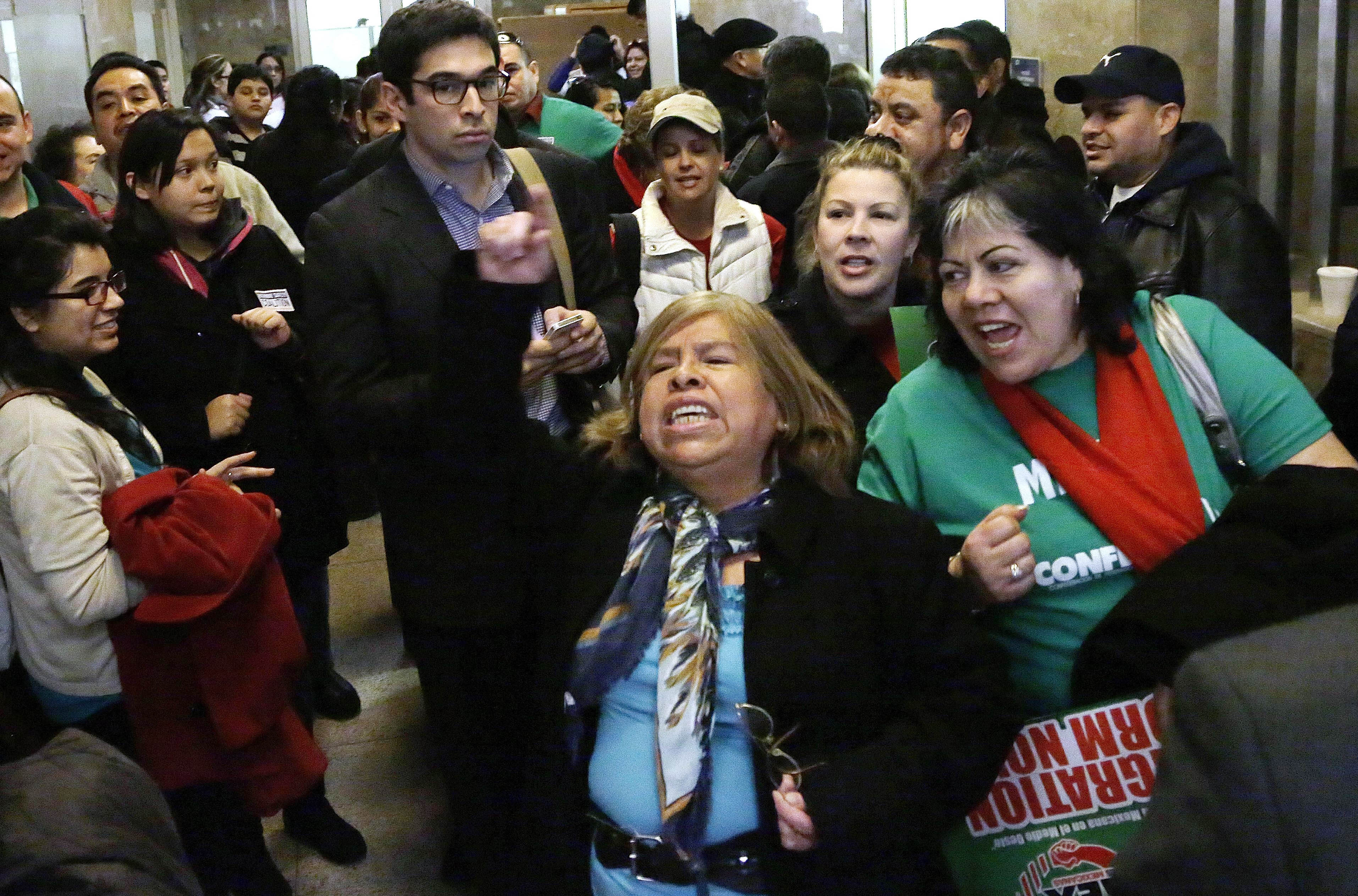 FILE - In this Jan. 7, 2013 file photo, supporters of granting illegal immigrants drivers licenses cheer after a House committee hearing at the Illinois State Capitol in Springfield. The House passed the legislation Jan. 8 and Gov. Pat Quinn is expected to sign the legislation Sunday, Jan. 27. As Illinois becomes the fourth and most populous state to issue driver's licenses to illegal immigrants, the initiative is still nagged by concerns it has enough safeguards to avoid the identity fraud and other pitfalls faced by the three other states with similar laws. (AP Photo/Seth Perlman, File)