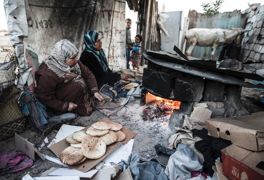 Palestinian women bake bread next to their makeshift home in the Khan Yunis refugee camp in the southern Gaza Strip on April 19, 2017 (AFP Photo/MAHMUD HAMS)