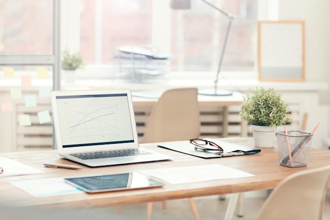 Background image of laptop on wooden table in modern office interior, workplace design concept, copy space