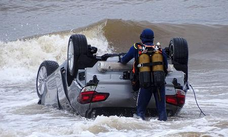 Police divers examine a turned-over car in the sea off Sainte Maxime beach, France October 11, 2018 in this image obtained from social media. Alexandre Houisse via REUTERS