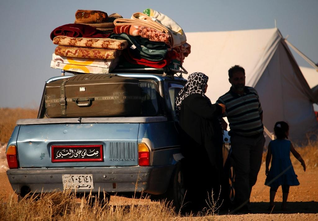 Displaced Syrians from the Daraa province fleeing shelling by pro-government forces wait in a makeshift camp to cross the Jordanian border, near the town of Nasib, southern Syria (AFP Photo/Mohamad ABAZEED)
