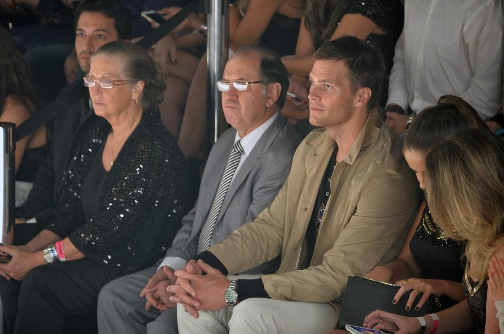 Brazilian supermodel Gisele Bundchen's husband, NFL star Tom Brady (R), watches as his wife strides the catwalk for the last time at the Colcci show during the 2016 Summer collections of the Sao Paulo Fashion Week on April 15, 2015 (AFP Photo/Nelson Almeida)