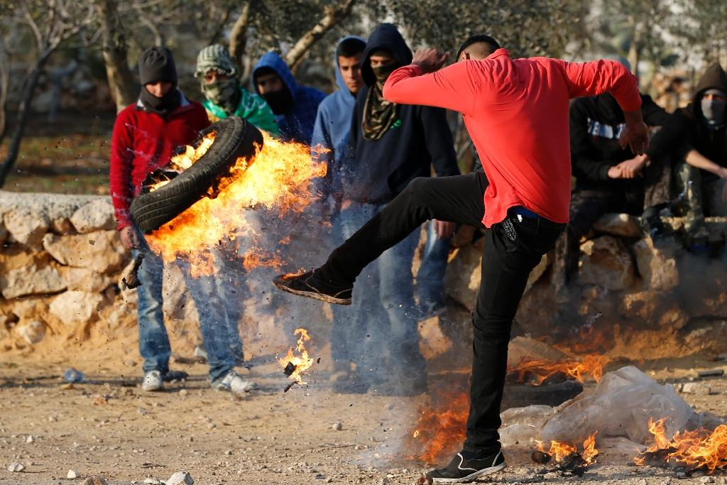Palestinian youths clash with Israeli soldiers on December 11, 2015 in the occupied West Bank village of Silwad after a demonstration to call for the remains of Palestinians killed by Israeli forces (AFP Photo/Abbas Momani)